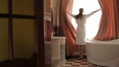 Girl opens curtains Stock Footage