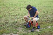 Stock Photo of adult man tying to ride on a small tricycle