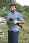 young lumberman in a forest with an axe in his hands - stock photo
