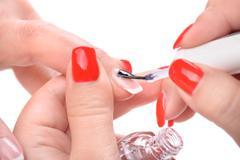 manicure, applying clear enamel - stock photo
