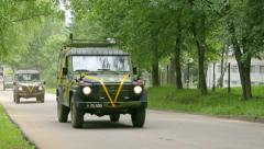 Military vehicles drive one after another down the road, pass by Stock Footage