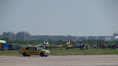 Air show, security car on runway, planes on the ground, crew members, pilots Stock Footage