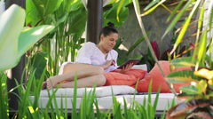 Woman lying in the garden and chatting on tablet Stock Footage