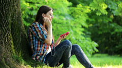 Young teenage woman listen to music on her smartphone in park HD Stock Footage
