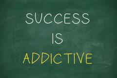 success is addictive handwritten on blackboard - stock illustration