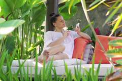 Happy man chatting on cellphone in exotic garden Stock Footage