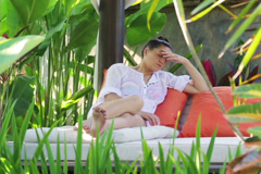 Sad woman sitting alone in exotic garden Stock Footage