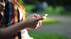 Woman hands texting, sending sms on smartphone in the park HD Stock Footage