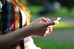 Woman hands texting, sending sms on smartphone in the park NTSC - stock footage