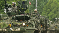 US soldiers drive in an armored fighting vehicles covered with camouflage nets Stock Footage