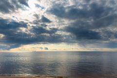 Blue rain clouds over a calm sea Stock Photos