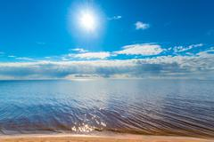 huge tranquil lake and the bright sun - stock photo