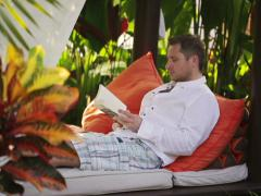 Man reading book and sitting in exotic garden Stock Footage