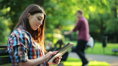 Young teenager with tablet computer sit on bench in park HD Stock Footage