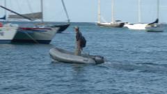Man pilots dingy across harbor Stock Footage