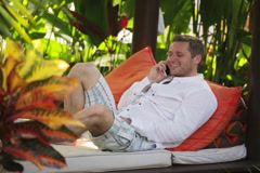 Happy man sitting on bed in the garden and chatting on cellphone Stock Footage