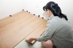 Young woman puts laminate flooring Stock Photos