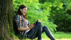 Young teenager watching movie on tablet computer in the park HD Stock Footage