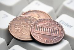 US coins on computer keyboard. Concept of e-commerce. Stock Photos