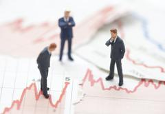 Financial crisis. Figures of businessman on financial charts Stock Photos