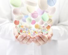 Stock Illustration of Colorful pills falling into open palms