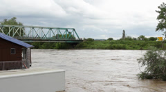 Fast river flows and flooding refrigerator car and raft, cloudy dark sky. Stock Footage