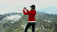 Stock Video Footage of Young woman uses a smartphone to video a beautiful view in the mountains HD