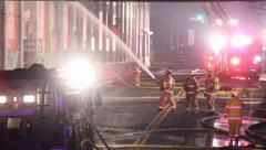 Fire fighters putting water on large factory fire Stock Footage