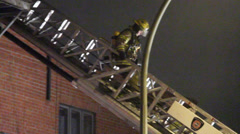 Fireman climbs down Montreal FD ladder Stock Footage