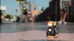 USA monkey toy walking on Hollywood boulevard 2 Stock Footage