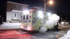 Yellow ambulance backing up in a street with snow Stock Footage