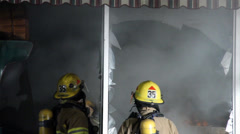 Fire fighters break the windows of a store Stock Footage