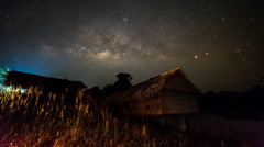 Milky Way Rising Over Bamboo Huts Stock Footage