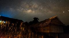 Milky Way Rising Over Bamboo Huts Pan up Stock Footage