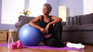 Stock Video Footage of Senior Black woman sitting on floor with exercise equipment