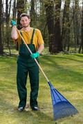 man raking leaves in garden - stock photo