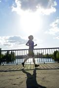 Young woman jogging over bridge at back light Stock Photos