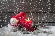 Stock Photo of Lighted red candle and Christmas cap with rippling artificial snow in front