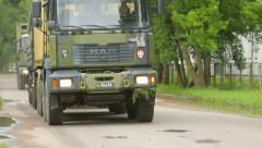 Military trucks drive down the road Stock Footage
