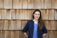 Portrait of creative business woman in front of wood shingle panelling Stock Photos
