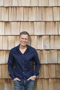 Portrait of creative business man in front of wood shingle panelling Stock Photos