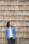 Portrait of young creative business woman in front of wood shingle panelling Stock Photos
