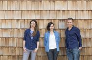 Stock Photo of Group picture of three creative business people in front of wood shingle
