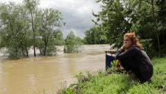 A girl and boy sitting and watching flood river from the coast. Stock Footage