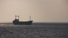 Boat silhouetted on horizon in the evening Stock Footage