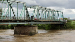 Turbulent river flows,people and car passing across the steel bridge. Stock Footage