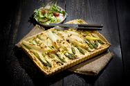 Stock Photo of Asparagus tart on jute and lettuce dish on dark wood