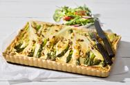 Stock Photo of Asparagus tart, cutlery and lettuce dish on white wood