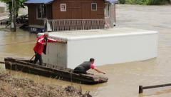 People in boat tie refrigerator car in flood river, natural disaster. Stock Footage