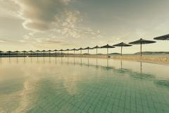 Croatia, Sibenik, Sunshades, Swimming pool of a hotel facility, Evening mood - stock photo